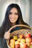 Young woman with a basket of ripe apples. Portrait of a woman holding a basket full of organic apples Stock Photos