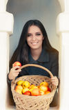 Young woman with a basket of ripe apples. Portrait of a woman holding a basket full of organic apples Stock Image