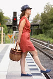 Young woman with basket standing at train station Stock Photo
