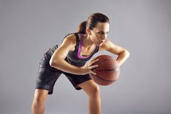 Young woman basketball player on grey background Stock Photos