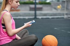 Young woman with basketball uses phone after training. Black screen. Young woman with basketball uses phone after training stock images