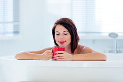 Young woman in bath with drink Royalty Free Stock Photography
