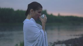 Girl drinking tea after a bath. Young woman after bath in the evening drinking tea from a thermos stock video footage