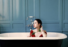 Young woman in bath with flower. Portrait of beautiful young woman sitting in bath holding a rose and relaxing Royalty Free Stock Photography