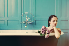 Young woman in bath with flowers stock images
