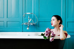 Young woman in bath with flowers Stock Photography