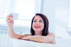Young woman in bath with phone Royalty Free Stock Photo