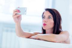Young woman in bath with phone Royalty Free Stock Image