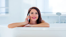 Young woman in bath with phone Royalty Free Stock Images