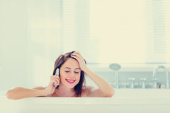 Young woman in bath with phone Stock Image