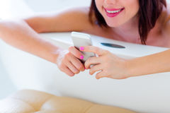 Young woman in bath with phone Royalty Free Stock Photography