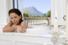 Young woman in bath, portrait, focus on candle in foreground Stock Photo