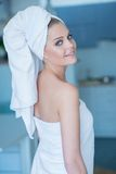 Young Woman in Bath Towel Looking Over Shoulder. Sexy Young Woman in Bath Towel Looking Over Shoulder at Camera  Waist Up Stock Photography