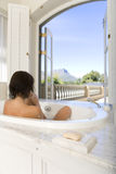Young woman in bath by window, rear view Stock Photo