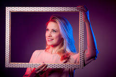 Young woman bathed with colorful light with frame Royalty Free Stock Photography
