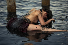 Young woman bathing in therapeutic water of mud estuary. Young woman bathing in therapeutic water of mud estuary, next there are wooden columns. Spa Stock Image