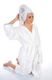 Young woman in bathrobe. Young woman relaxing in white bathrobe with towel around wet hair, studio background Stock Image