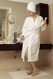 Young woman in bathrobe. In front of the mirror Royalty Free Stock Photo