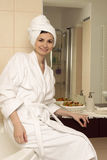 Young woman in bathrobe. In a modern bathroom Royalty Free Stock Images