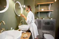 Woman applying mask on her face in the bathroom stock photo