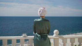 Young woman in bathrobe on balcony stock video footage