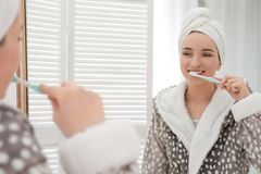 Young woman in bathrobe brushing teeth near mirror at home. Morning routine stock photos