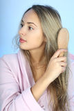 Young woman in bathrobe with comb Stock Photography