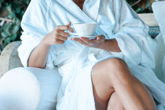 Young woman in a bathrobe with a cup of tea Royalty Free Stock Images