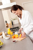 Young woman in bathrobe cutting orange in kitchen Royalty Free Stock Photo