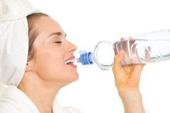Woman in bathrobe drinking from bottle with water royalty free stock photos
