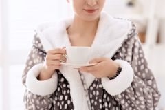 Young woman in bathrobe drinking coffee at home. Early morning royalty free stock images