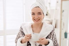Young woman in bathrobe drinking coffee at home. Early morning royalty free stock photos
