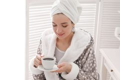 Young woman in bathrobe drinking coffee at home. Early morning stock photo