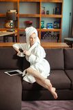 Young woman in bathrobe drinking coffee and reading on digital tablet stock images