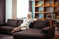 Young woman in bathrobe drinking coffee and reading on digital tablet stock photos
