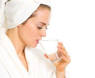 Young woman in bathrobe drinking pure water Stock Photography