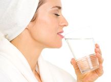 Young woman in bathrobe drinking water Royalty Free Stock Photography