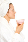 Young woman in bathrobe enjoying cup of tea Royalty Free Stock Photos