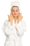 Young woman in bathrobe after facial treatment Royalty Free Stock Image