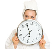 Young woman in bathrobe hiding behind clock Stock Photo