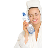 Young woman in bathrobe holding bottle with water Stock Photo