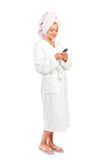 Young woman in bathrobe holding a mobile phone Stock Image