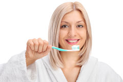Young woman in a bathrobe holding a toothbrush Stock Image