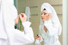 Young woman in bathrobe in hotel bathroom Stock Photo