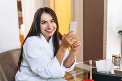 Young woman in bathrobe in hotel room using mobile phone. Relaxed after taking a bath royalty free stock photography