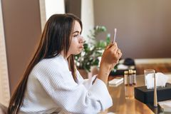 Young woman in bathrobe in hotel room using mobile phone. Relaxed after taking a bath stock photo