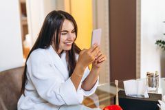 Young woman in bathrobe in hotel room using mobile phone. Relaxed after taking a bath royalty free stock photos