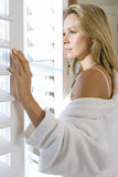 Young woman in bathrobe looking out window with shutters, close-up, side view Stock Photography