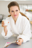 Young woman in bathrobe with milk and magazine Stock Image