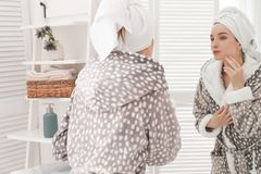 Young woman in bathrobe near mirror at home. Morning routine royalty free stock photography